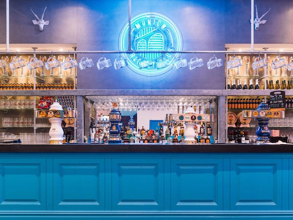 Munich Cricket Club - bar painted in blue with neon sign above it