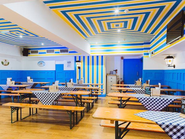Munich Cricket Club - bar seating area painted in blue, white and yellow