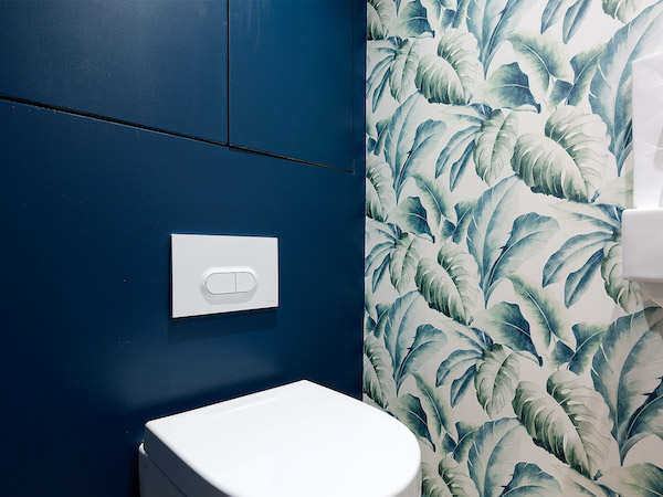 Pelham Road - bathroom painted in dark blue with floral wallpapered feature wall